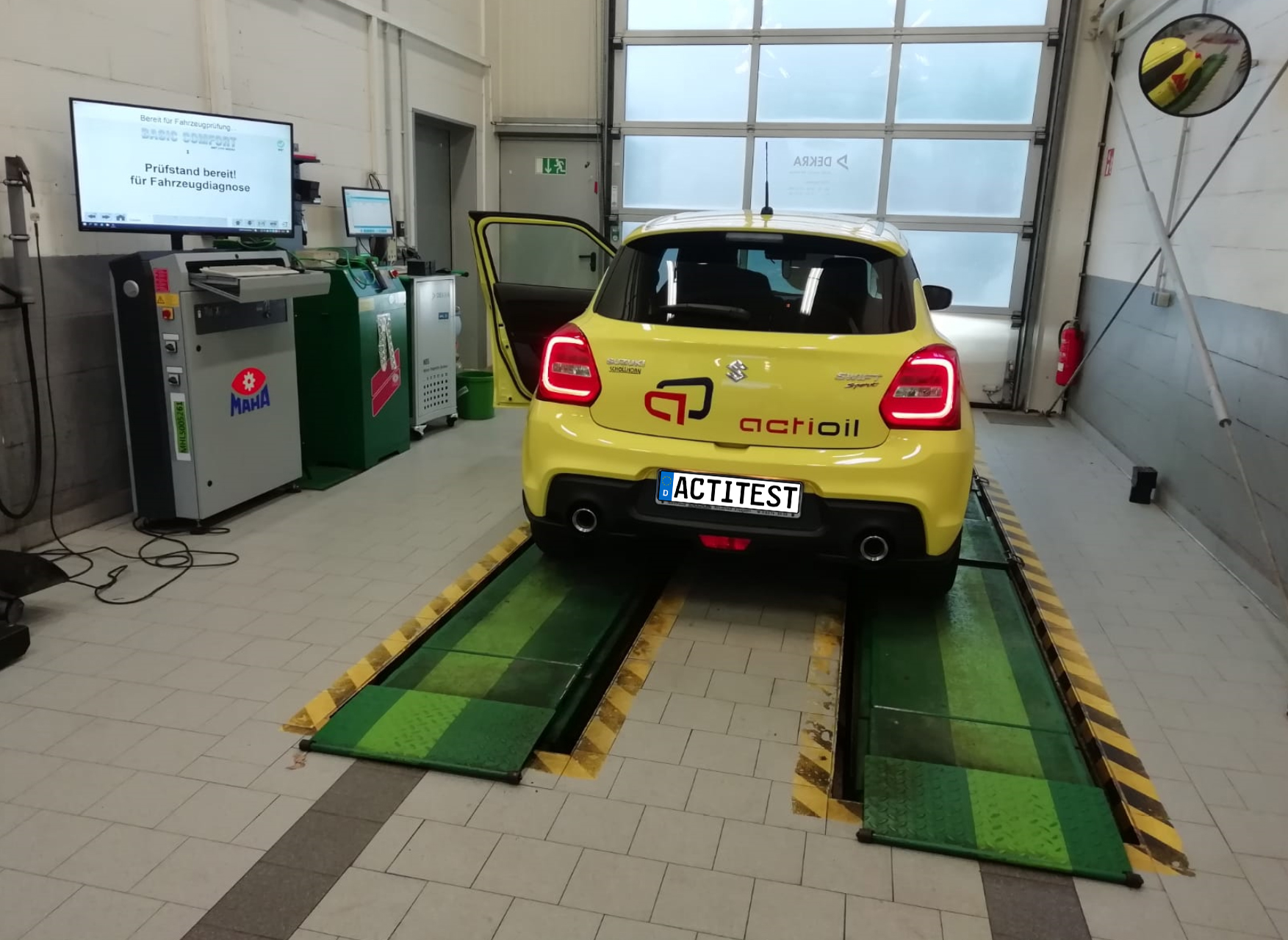 Yellow Suzuki car in a test area from DEKRA. Measurement of fuel and environment efficiency